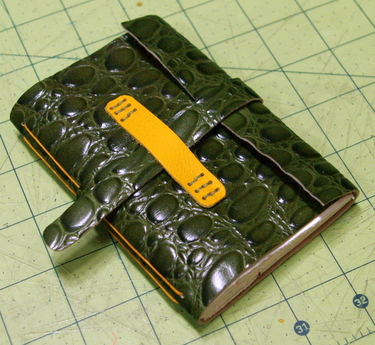 Green and yellow handmade leather journal with strap closure