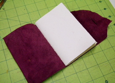 Opened magenta handmade leather journal with button closure
