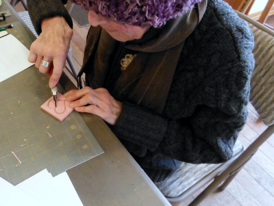 Student hand carving a rubber stamp
