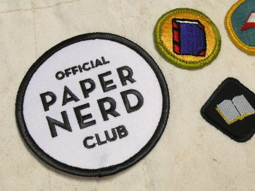 Paper Nerd Club patch by Constellation & Co. and other badges