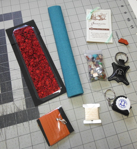A marbled bookmark from Chena River Marblers, a small roll of bookcloth, a pack of bookplates, a leather key chain from Harmatan Leather, a tape measure key chain from Harmatan Leather,  a small bag of beads