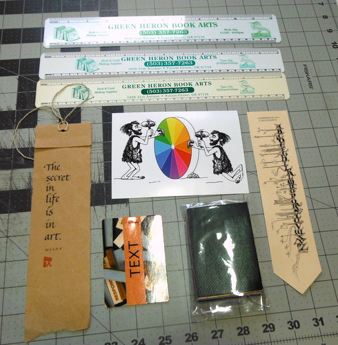 Three rulers from Green Heron Book Arts, a batch of paper samples from Legion Paper, two paper bookmarks, a postcard, and a card from the Artist's Book Ideation Cards by Barbara Tetenbaum and Julie Chen