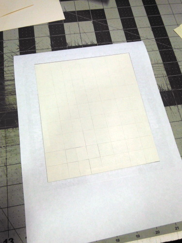 White Tyvek with double-sided adhesive sheet mounted on the back, taped to a sheet of paper