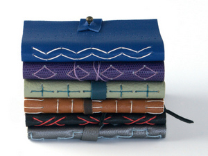Pile of handmade leather journals by Elissa Campbell of Blue Roof Designs