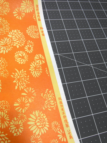 Orange letterpressed paper with flowers with Japanese writing on the edge