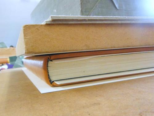 Hand-sewn leather-bound book under weight