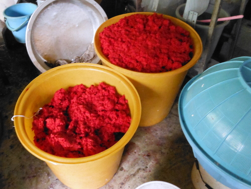 Plastic buckets full of red paper pulp